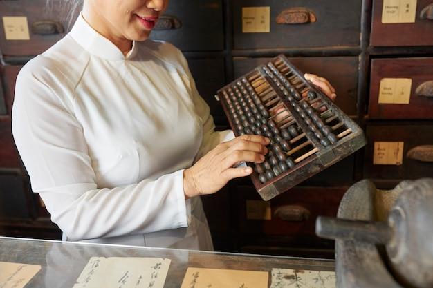 古い伝統的な薬局で働く女性