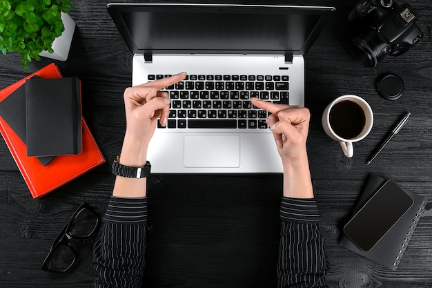 사무실 테이블에서 일하는 여성은 인간의 손 노트북 키보드 커피 스마트폰 한 잔의 평면도를 볼 수 있습니다...