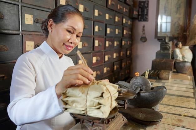 伝統的な中国の薬局で働く女性