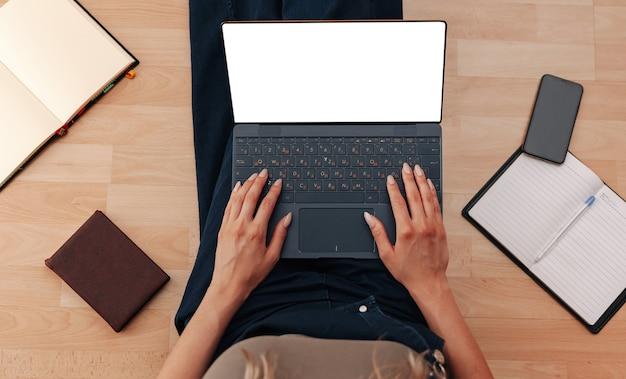 Женщина, работающая за ноутбуком с белым экраном, сидя на полу