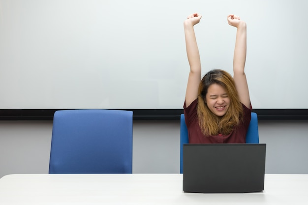 Woman working by laptop in office with happy