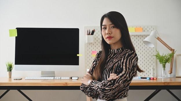 Woman working concept, female creative artist looking at camera in stylish office.
