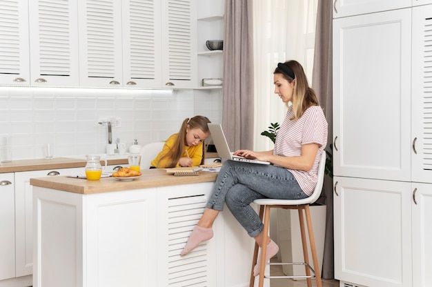 Woman working at desk with girl full shot