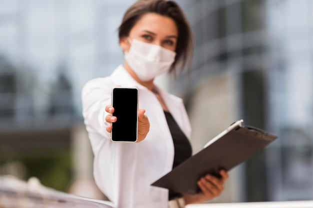 Woman working during pandemic outdoors showing smartphone while holding notepad