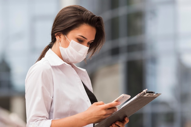 Woman working during pandemic outdoors with smartphone and notepad