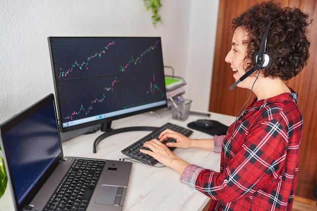 Женщина, работающая из дома торговцем, печатает на клавиатуре, глядя на монитор с графикой