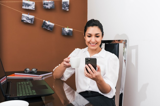 Woman working from home on coffee break while checking her cell phone