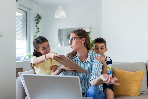 ソファで幼い息子と娘と一緒に検疫中に自宅で仕事をし、注意を求めて叫んでいる女性