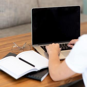 ノートパソコンとノートブックで社会的距離のために自宅で働く女性