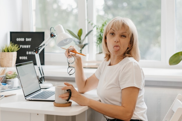 Woman working from home on laptop and sticking out tongue