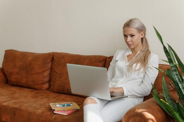 Женщина работает дома, сидя на диване