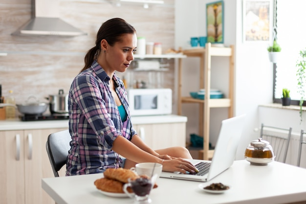 Woman working from home using laptop in kitchen during breakfast