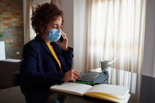 医療用フェイスマスクを着用して在宅勤務の女性