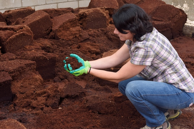 Woman working in the garden center, composting,
