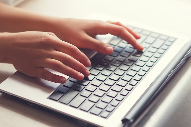 Woman working at home office hand on keyboard close up, toned