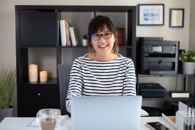 Woman working at home office. smiling and looking at camera.