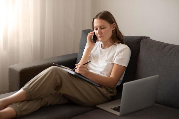 Donna che lavora a casa sul divano durante la quarantena con smartphone e laptop