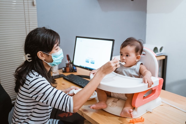 Woman working at home and taking care of his baby