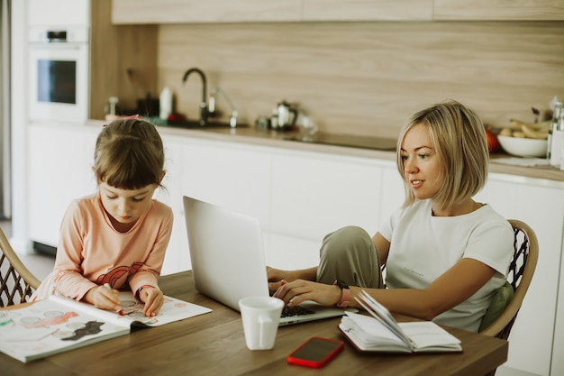 Woman working at home with her little daughter sitting near and drawing