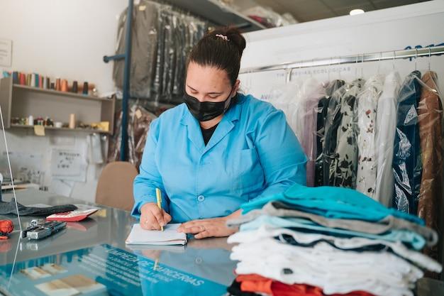 다림질 후 옷걸이에 옷을 입고 세탁소에서 일하는 여자
