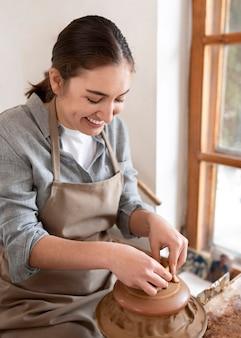 陶器の職場で働く女性