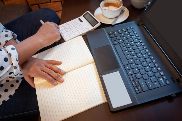 Женщина, работающая в кафе, имеет чашку кофе, ноутбук, калькулятор и документы. концепция стартапов и фрилансеров