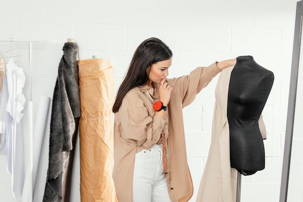 Женщина работает в своей мастерской по дизайну одежды в одиночестве