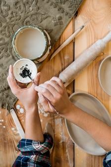 彼女の陶器のワークショップで働く女性