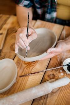 Женщина, работающая в своей гончарной мастерской
