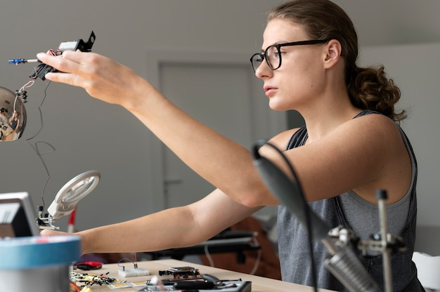 創造的な発明のために彼女のワークショップで働いている女性