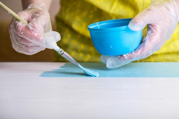 彼女のワークショップで働いている女性、青い木の板を描く