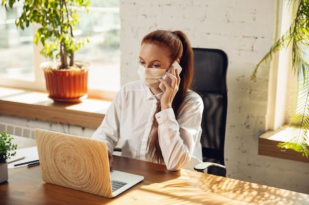 コロナウイルスまたはcovid-19検疫中に一人でオフィスで働く女性、フェイスマスクを着用