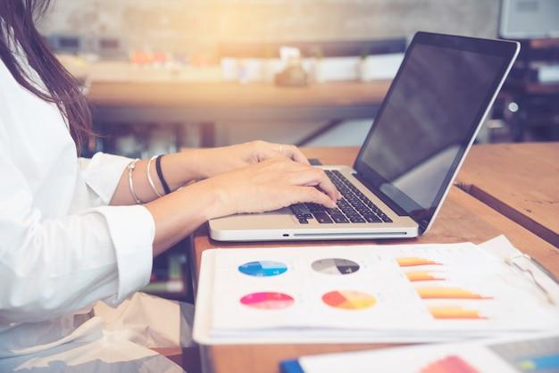 Женщина, работающая в офисе, используя ноутбук и таблицу excel