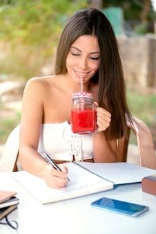 庭で働いて、ジュースを書いたり飲んだりしている女性