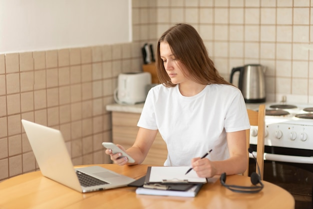 Женщина работает на кухне во время карантина с ноутбуком и смартфоном