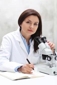 Женщина, работающая в лаборатории с микроскопом