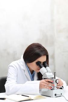 顕微鏡でラボで働く女性