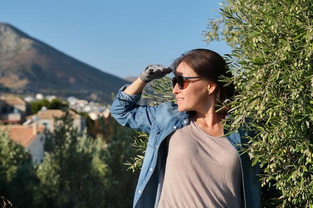 オリーブガーデン、山を背景に働く女性