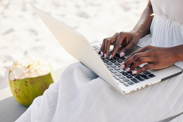 Woman working on laptop on beach