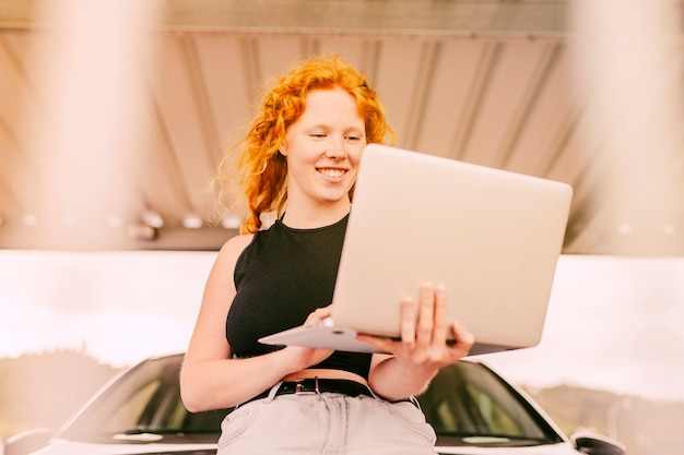 Woman working on laptop beside car outdoors
