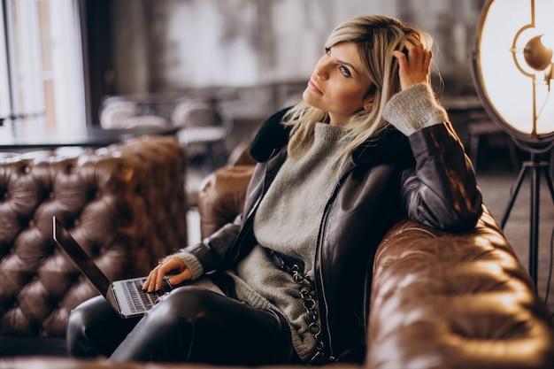 Donna che lavora al computer portatile in un bar e allenatore seduto