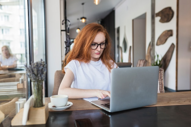 Woman working on laptop in cafe