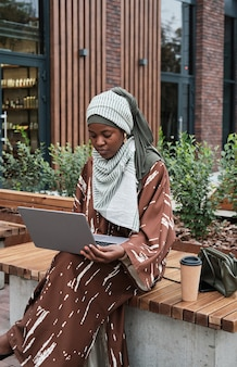 Woman working on laptop in the city