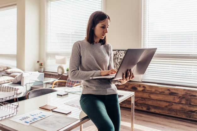 Woman working on laptop computer sitting on table