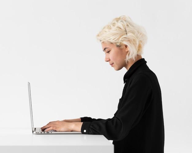Donna che lavora al colpo medio del computer portatile