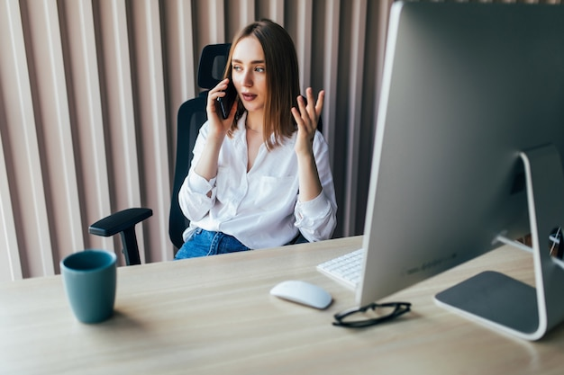 Woman working on laptop at office while talking on phone