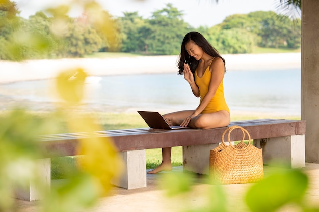 Woman working on laptop outdoors full shot