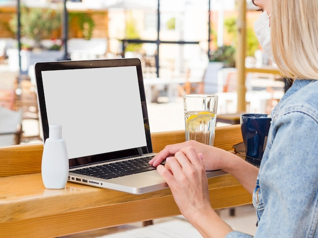 Woman working on laptop outdoors with hand sanitizer