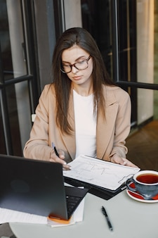 Woman working on a laptop in a street cafe. wearing stylish smart clothes -  jacket, glasses