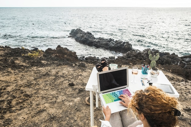 Woman working on laptop with colorful keyboard while sitting at the sea coast with her feet resting on table desk in front of ocean. businesswoman working on laptop in front of beautiful sea